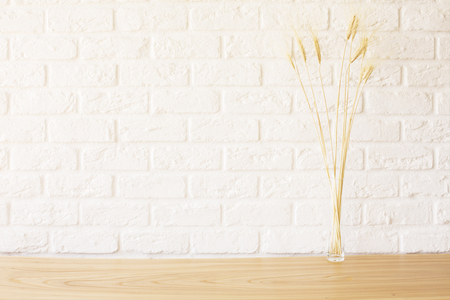 Front view of wheat spikes on wooden desktop and white brick background. Mock up Stock Photo