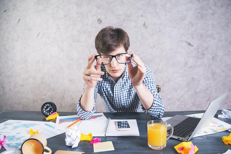 oficina desordenada: hombre agotado loco sentado en el escritorio de oficina desordenada y mirando a la c�mara a trav�s de anteojos