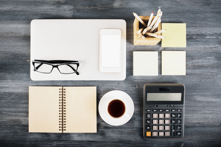 neatly: Dark wooden desktop with neatly organized laptop, coffee cup, notepad, blank white smartphone, glasses, calculator and other items. Top view, Mock up