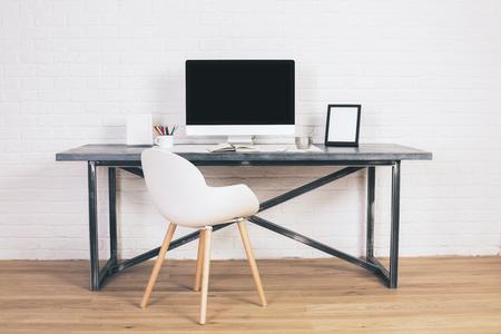portada: Vista frontal de la silla y blanca del diseñador moderno escritorio con pantalla en blanco y marcos de cuadros en el fondo de ladrillo blanco. Bosquejo