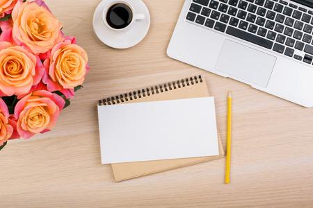 Bovenaanzicht van creatieve werkplek met prachtige bloemen, laptop toetsenbord, kopje koffie en blanco papier. Mock up Stockfoto