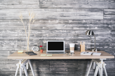 front desk: Front view of hipster workpspace with blank laptop, various stationery items and wheat spikes on wooden wall background. Mock up Stock Photo