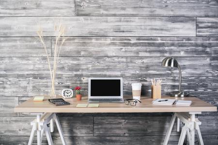 articulos oficina: Vista frontal de workpspace inconformista con el ordenador portátil en blanco, varios artículos de papelería y espigas de trigo en el fondo de la pared de madera. Bosquejo