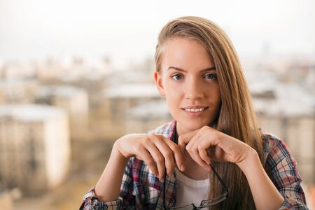 blurr: Portrait of smiling young woman with glasses in hand on blurr y city background