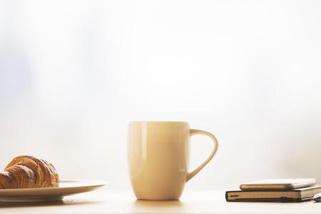 Close-up van lange koffiekop, croissant op bord en notitieblok bovenop de telefoon