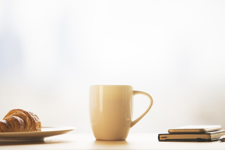 Closeup of tall coffee cup, croissant on plate and notepad on top of phone