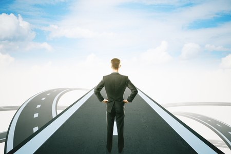 standing businessman: Success concept with thoughtful businessman standing on highway road leading to bright sky. 3D Rendering Stock Photo