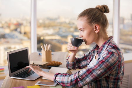 casually: Casually dressed female enjoying coffee using laptop computer.