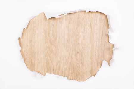 revealing: Torn white paper revealing wooden surface. Mock up Stock Photo