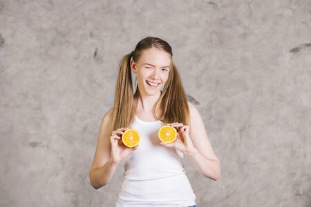 ponytails: Winking young woman with ponytails playing with two orange halves
