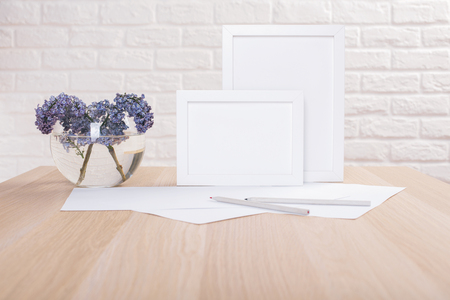 paper sheets: Lilac in bowl with water, two blank picture frames, paper sheets and pencils on wooden table and white brick wall background. Mock up