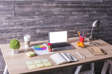 empty table: Closeup of modern creative desktop with blank white laptop, stationery items, plants and other objects on wooden wall background. Mock up