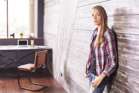 casually: Casually dressed girl standing in office interior against wooden wall