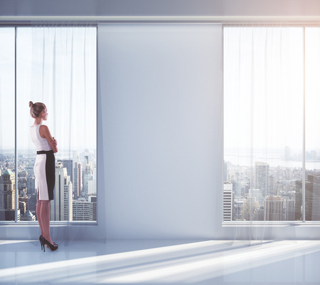 looking at view: Businesswoman looking outside of window in empty interior with New York city view and blank wall. Mock up, 3D Rendering