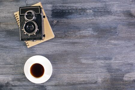 retro dark: Top view of dark wooden desktop with coffee cup, retro camera and notepad. Mock up