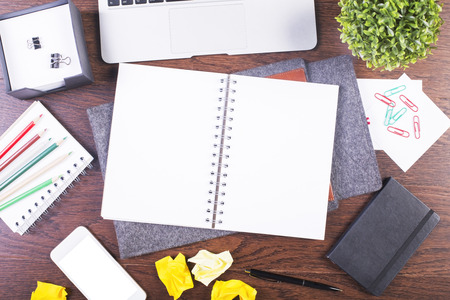 creative tools: Top view of creative dark wooden desktop with blank spiral copybook, white smartphone and various office tools. Mock up Stock Photo