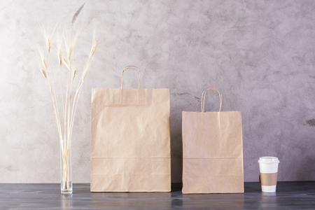 take away: Take away food bags, wheat spikes and coffee cup on concrete background. Mock up Stock Photo