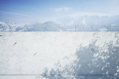 shadows: Concrete prison wall with shadows and snowy mountains view. Mock up, 3D Rendering Stock Photo