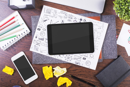 creative tools: Top view of creative dark wooden desktop with blank tablet, business sketch, smartphone and various office tools. Mock up