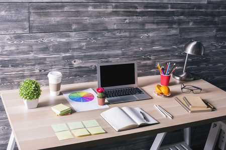 Lateral de escritorio creativa moderna con ordenador portátil en blanco, artículos de papelería, plantas y otros objetos en el fondo de la pared de madera. Bosquejo