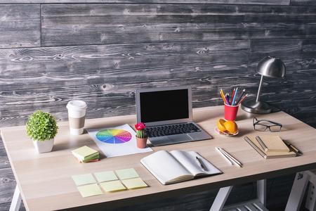 Sideview di moderno desktop creativo con il bianco del computer portatile, articoli di cancelleria, piante e altri oggetti sullo sfondo parete di legno. Modello