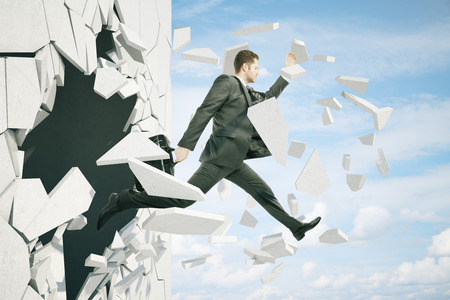 broken through: Business breakthrough success concept with businessman jumping through wall on sky background