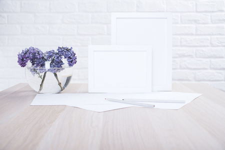 Lilac in bowl with water, two blank picture frames, paper sheets and pencils on wooden desktop and white brick wall background. Mock up
