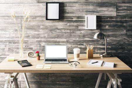 Bureau de bois créatif avec un ordinateur portable blanc vierge, divers articles de papeterie, tasses à café et cadres vierges suspendus au-dessus du mur sombre. Mock uo