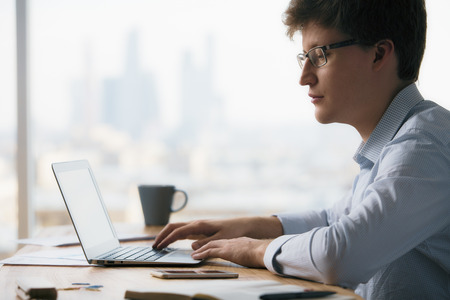 Sideview of caucasian businessperson using laptop on wooden desktop with smartphone and other items on blurry city background