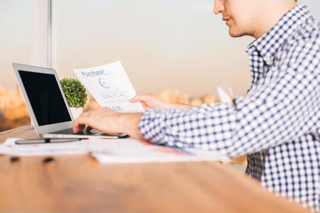 cuadro sinoptico: Joven cauc�sica informaci�n de la copia Hombre de hoja de papel con el informe de negocio a su ordenador. fondo iluminado por el sol de la ciudad. Bosquejo Foto de archivo