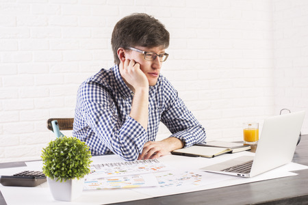 successful man: Tired caucasian male resting chin on hand at office desk and looking at a laptop display Stock Photo