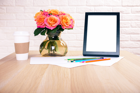 table decoration: Front view of wooden desktop with roses, coffee cup, blank picture frame and colorful pencils on white brick wall background. Mock up