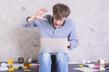 working desk: Crazy frastrated businessman sitting on messy office desktop about to hit his laptop with hand