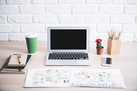 Primo piano del tavolo pantaloni a vita bassa creativa con schermo in bianco del computer portatile, abbozzo di business, tazza di caffè, cactus e altri oggetti su sfondo bianco muro di mattoni. Modello