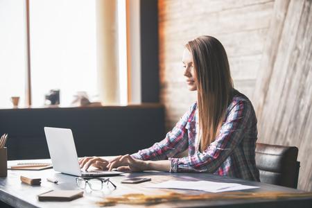 Jeune femme utilisant un ordinateur portable sur le bureau avec divers articles dans l'intérieur