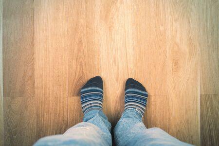 piernas hombre: Vista superior de las piernas del hombre en pantalones vaqueros y calcetines en el piso de madera