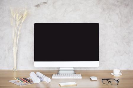 Twórczy pulpit z monitora komputera puste, kolce pszenicy, okulary, inteligentny telefon, szkice i filiżanka kawy na tle konkretnych. Makieta