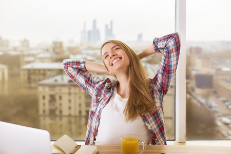 hands on head: Beautiful smiling young woman sitting at office desk with hands behind head on city background