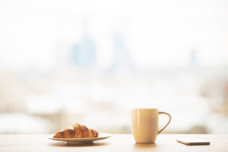 Tabla con la taza de café de altura, la placa con el croissant y el teléfono inteligente en el fondo borroso de la ciudad