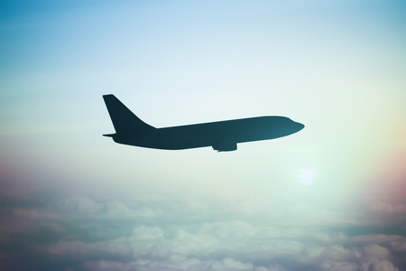 sunlight sky: Airplane silhouette in cloudy sky with sunlight