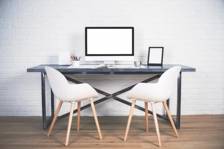 portada: Dos sillas junto a la mesa de diseño con pantalla en blanco y otros artículos en suelo de madera y fondo de ladrillo. Bosquejo Foto de archivo
