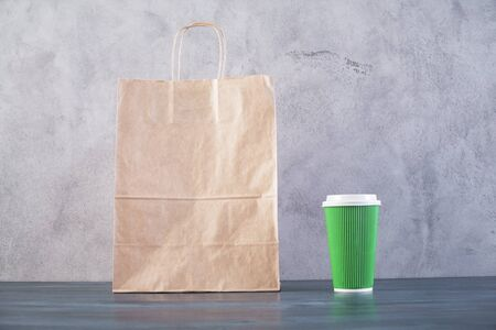 take away: Front view of blank take away food bag and green coffee cup on wooden surface and concrete background. Mock up