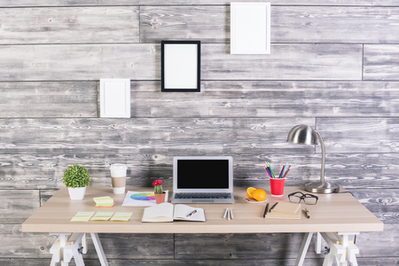 Modern designer workplace with blank laptop, picture frames above, plants, stationery and other items. Mock up