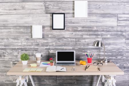 Moderne Designer-Arbeitsplatz mit leeren Laptop, Bilderrahmen oben, Pflanzen, Briefpapier und andere Einzelteile. Attrappe, Lehrmodell, Simulation Standard-Bild