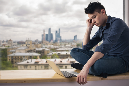 man behind: Handsome young man sitting on windowsill with city view and looking at laptop screen