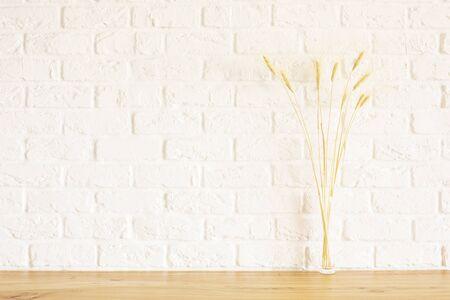 Vooraanzicht van tarwe spikes op houten oppervlak en witte bakstenen achtergrond. Mock up