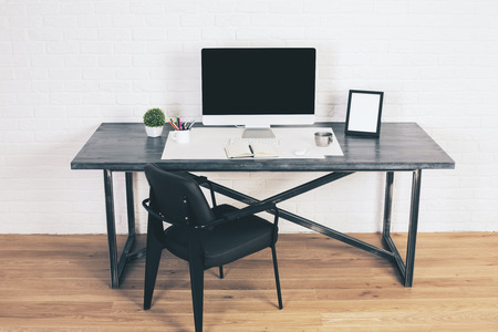 designer chair: Black chair next to designer desk with blank computer screen, frame and other items on wooden floor with white brick wall in the background. Mock up