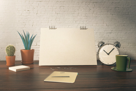Closeup of office table with blank card, plants, coffee cup, alarm clock and stationery items on white brick background. Mock up, 3D Rendering Stock Photo