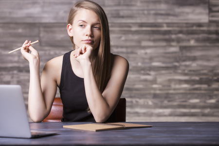 hardworker: Front view of thoughtful girl sitting at wooden desktop with laptop and notepad Stock Photo