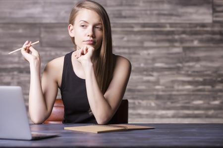 niña pensando: Vista frontal de la joven reflexiva sentado en el escritorio de madera con el ordenador portátil y el bloc de notas